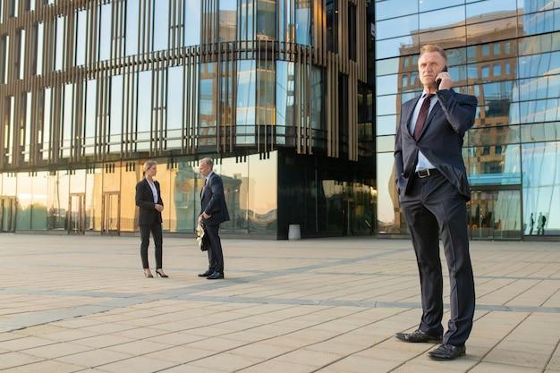 성공적인 사업가 사무실 양복을 입고 야외에서 휴대 전화에 대 한 얘기. 기업인과 도시 배경에서 유리 외관 건물. 공간을 복사하십시오. 비즈니스 커뮤니케이션 개념