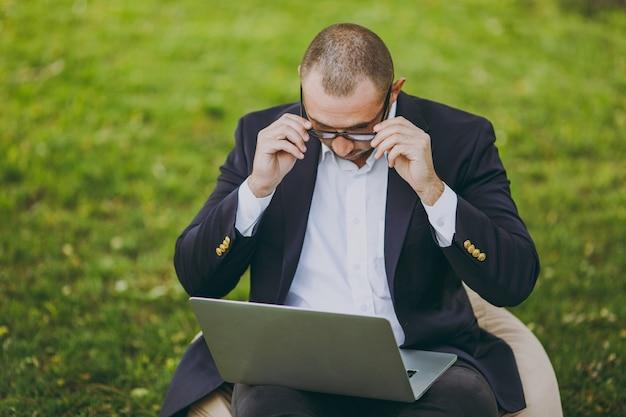 Successful businessman in white shirt, classic suit, correct glasses. man sit on soft pouf, work on laptop pc computer in city park on green lawn outdoors on nature. mobile office, business concept.