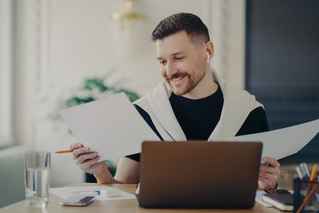 Successful businessman in wireless earphones, analyzing documents and looking satisfied with business results while working from home. male office worker sitting at his workplace and feeling happy
