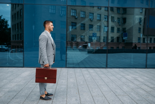 Successful businessman with briefcase at the office building in downtown.