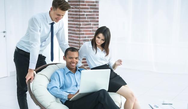 Успешный бизнесмен со своими помощниками в обсуждении информации из офисной жизни ноутбука