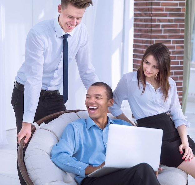Успешный бизнесмен со своими помощниками в обсуждении информации с ноутбука