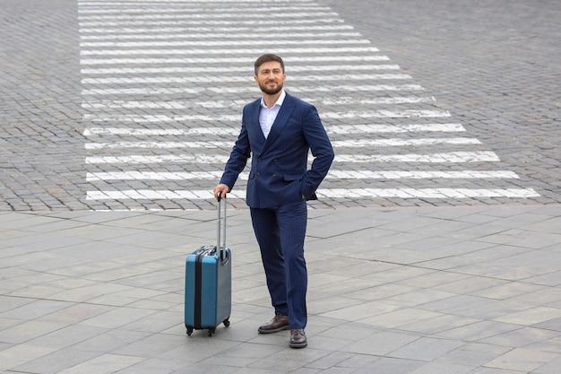도시 거리 횡단보도에서 여행 가방을 들고 성공한 사업가