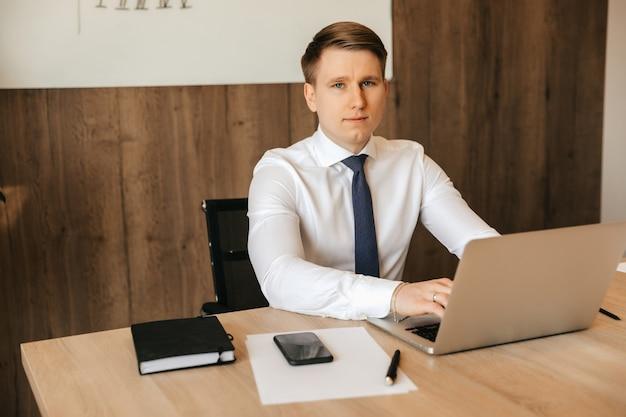 彼のオフィス、オフィスワークでラップトップで働く成功した実業家。