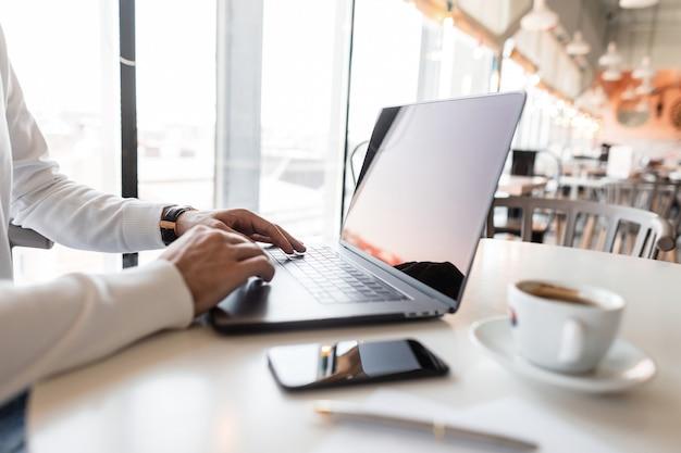 카페에서 노트북 뒤에서 일하는 성공적인 사업가