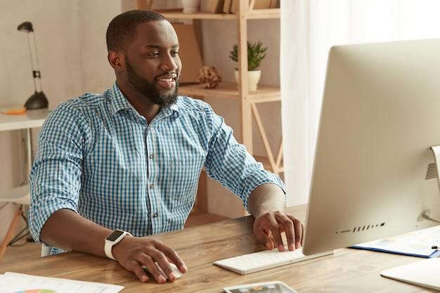 원격으로 작업하는 성공적인 사업가 셔츠에 쾌활한 젊은 아프리카계 미국인 남자