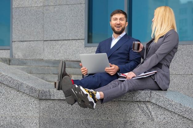 성공적인 사업가 남녀가 비즈니스 프로젝트에 대해 논의하는 문서와 노트북을 손에 들고 비즈니스 건물의 계단에 앉아 있습니다.