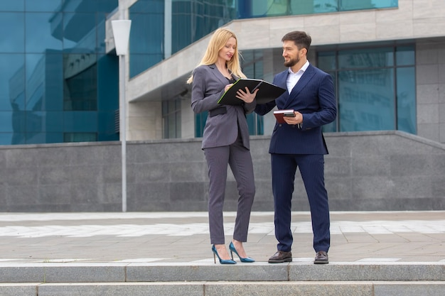 Successful businessmen partners man and woman next to business building with documents in their hands discussing business projects