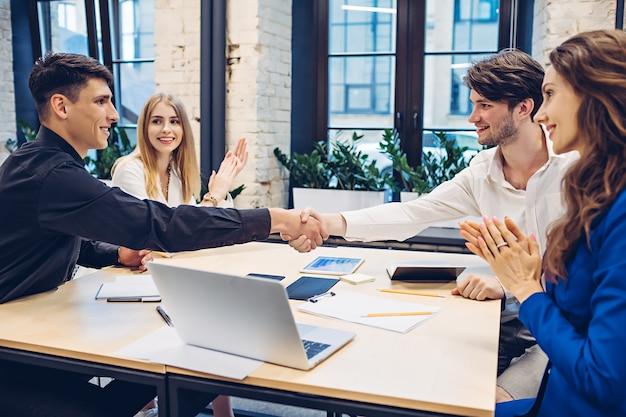 ビジネスウーマンがオフィスのテーブルで手をたたく間握手成功したビジネスマン