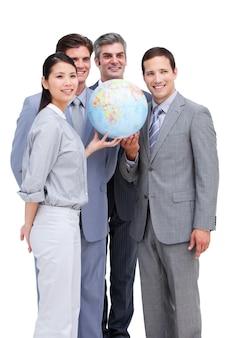 Successful businessteam looking at a terrestrial globe