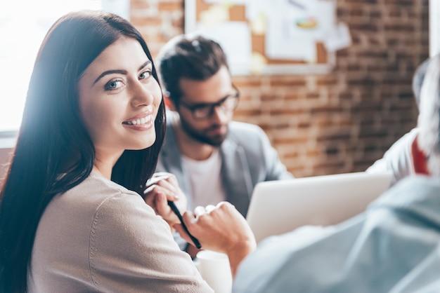 成功した実業家。彼女の同僚がバックグラウンドで何かを話している間、笑顔でカメラを見ている陽気な若い女性のクローズアップ