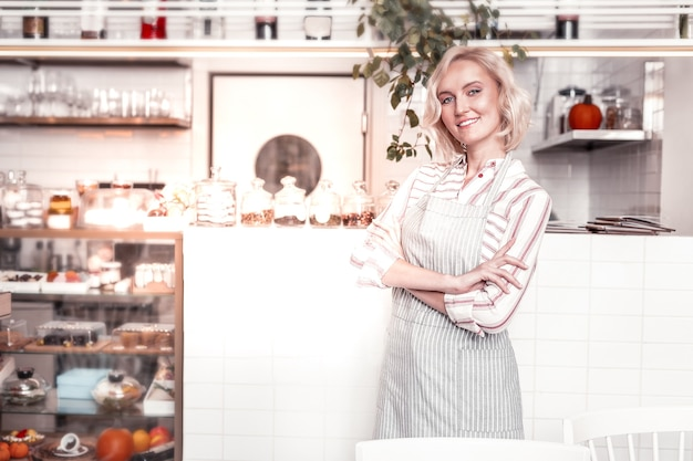 Successful businesswoman. confident good looking woman standing cross handed while working in her bakery