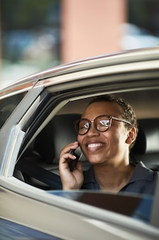 Successful businesswoman in eyeglasses talking on mobile phone and laughing during her travelling by car