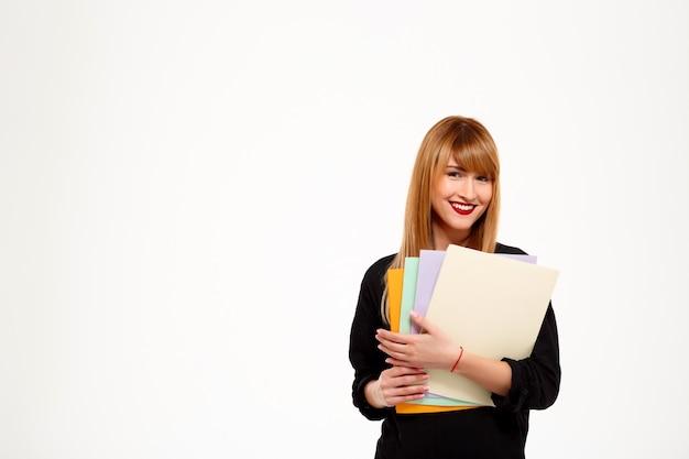 Cartelle della tenuta della donna di affari riuscite e sorridere sopra lo spazio bianco della copia della parete.