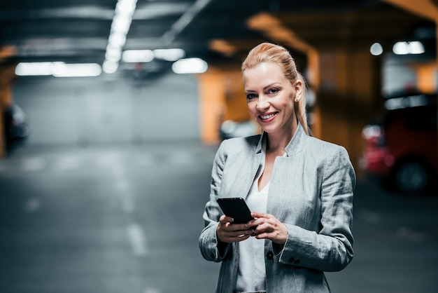 Successful businesswoman holding smartphone and looking at camera in underground car parking.
