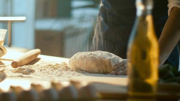 Успешная бизнес-леди с удовольствием месит тесто на деревянном столе