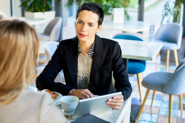 Successful businesswoman leading meeting in cafe