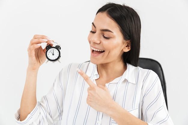 オフィスの肘掛け椅子に座って、白い壁に隔離された小さな目覚まし時計を保持しながら喜んで成功した実業家