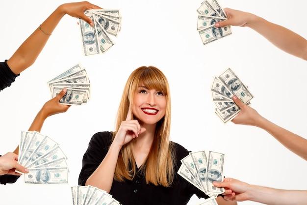 Imprenditrice di successo sorridente tra i soldi sul muro bianco