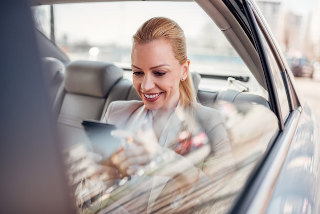 Successful businesswoman texting on smart phone while sitting on back seat in the car.