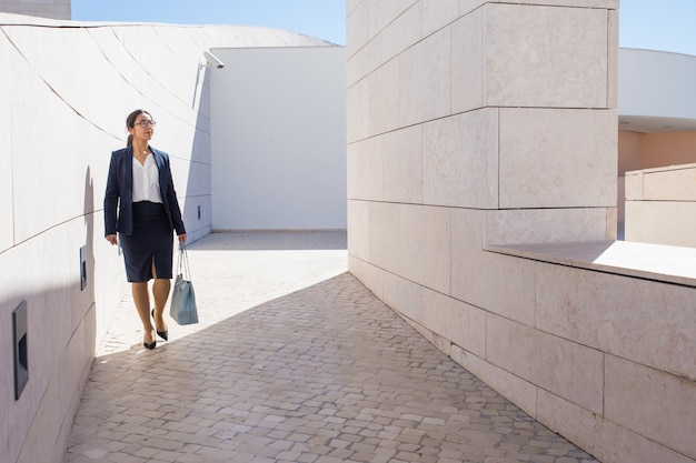 Successful businesswoman walking around modern business center