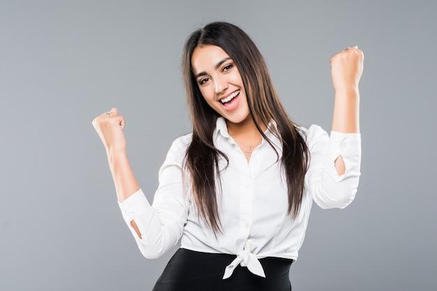 Imprenditrice di successo con le braccia in alto isolato su un bianco