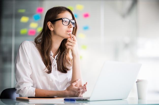 Успешная деловая женщина работает на портативном компьютере и думает над новыми идеями в своем офисе, одетая в белую одежду
