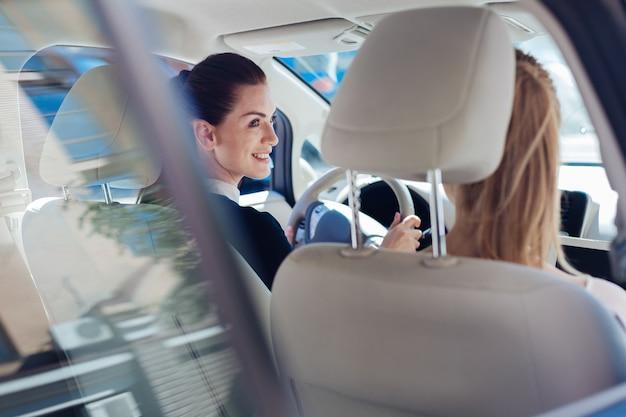 Успешные предпринимательницы. в восторге от милых счастливых женщин-предпринимателей, сидящих в машине и смотрящих друг на друга по дороге на работу