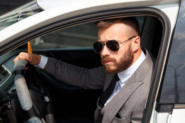 Успешный кавказский мужчина в строгом костюме за рулем автомобиля