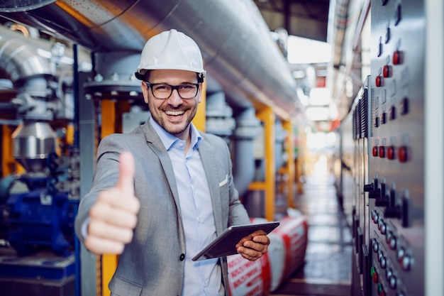 Successful caucasian supervisor in suit and with helmet holding tablet and showing thumbs up while standing next to dashboard in power plant.