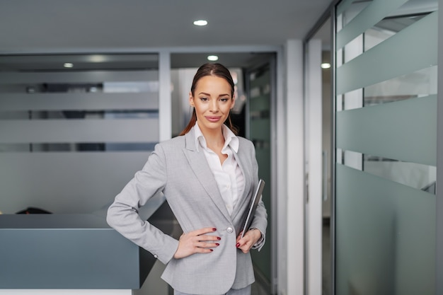 Successful caucasian young businesswoman standing inside corporate firm, holding hand on hip and in other hand holding tablet.
