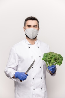 Successful chef in protective mask, gloves and white uniform going to cut fresh broccoli with sharp knife before cooking vegetable soup