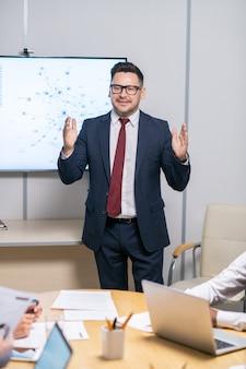 ビジネスコースのポイントを説明するフォーマルウェアの成功したコーチ