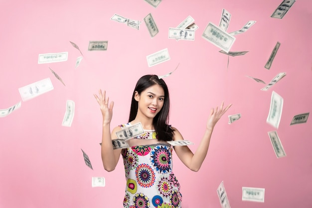 Successful concept, portrait of young woman with falling dollars banknotes in the ai