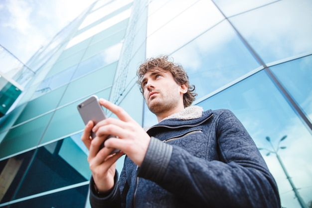Successful confident handsome attractive young man in black jacket using mobile phone standing near glass building