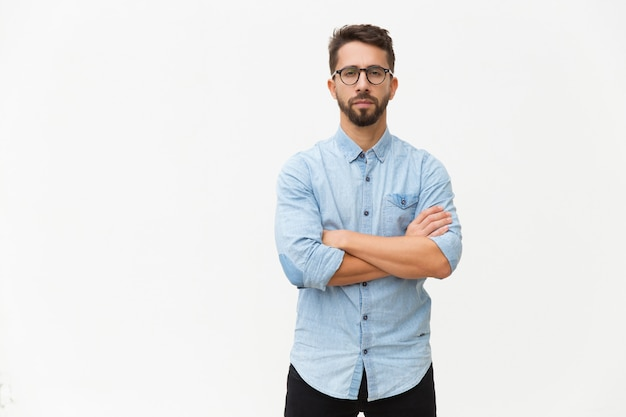 Successful confident male entrepreneur posing with arms folded