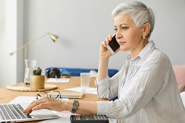 Успешная уверенно зрелая деловая женщина с седыми короткими волосами, работающая в стильном офисном интерьере, с помощью ноутбука и калькулятора, разговаривает с деловым партнером по мобильному телефону. люди, возраст и род занятий