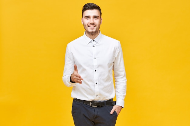 Successful confident young man in white formal shirt and classical trousers smiling and reaching out hand to shake yours, making welcoming and greeting gesture, ready to make agreement