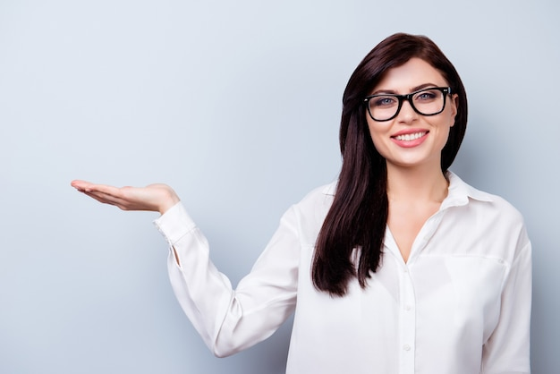 新製品を提示する成功した自信を持って若い女性