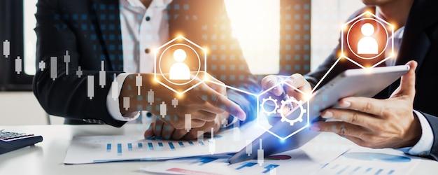 성공적인 연결 개념, 법률 및 사업가 고문, 두 명의 사업가가 이야기하고, 사무실에서 태블릿에 대한 투자 및 마케팅을 분석할 계획입니다.