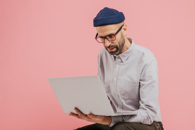 Successful copywriter types publication, reads information, holds laptop computer, wears glasses