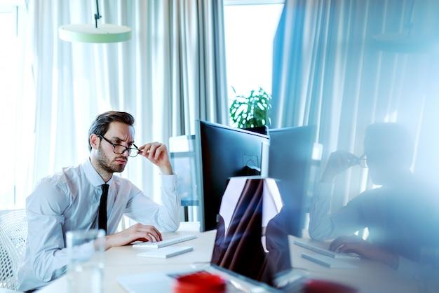 彼のオフィスに座っている間仕事にデスクトップコンピューターを使用して深刻な顔をして成功した企業のビジネスマン。