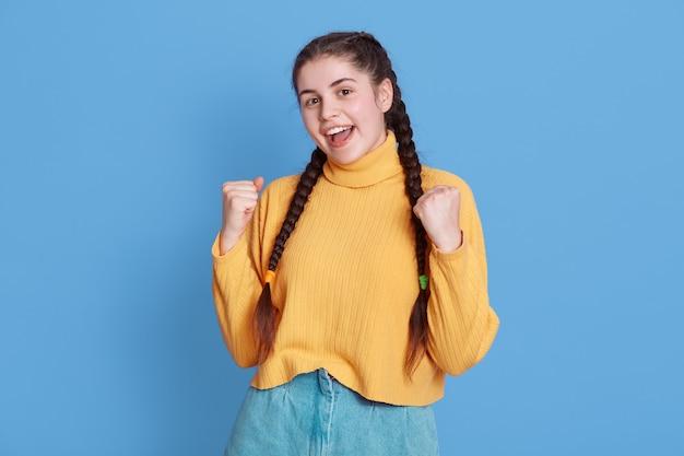 成功した黒髪の女子学生は非常に幸せで、拳を握りしめ、黄色いセーターとおさげ髪を着て、最終的に勝利を叫び、青い壁の上に孤立して立っています