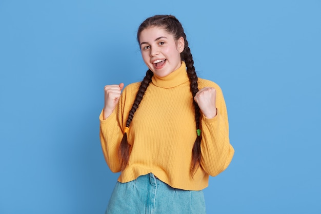 Successful dark haired female student being very happy, clenches fists, exclaims finally victory, wearing yellow sweater and pigtails, stands isolated over blue wall