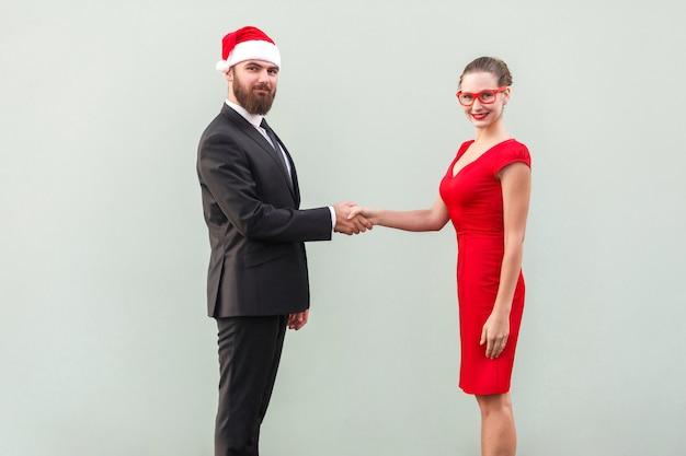 Удачная сделка. рукопожатие, отмечаем контракт. хорошо одетые деловые люди, глядя в камеру и зубастую улыбку. студийный снимок, серый фон
