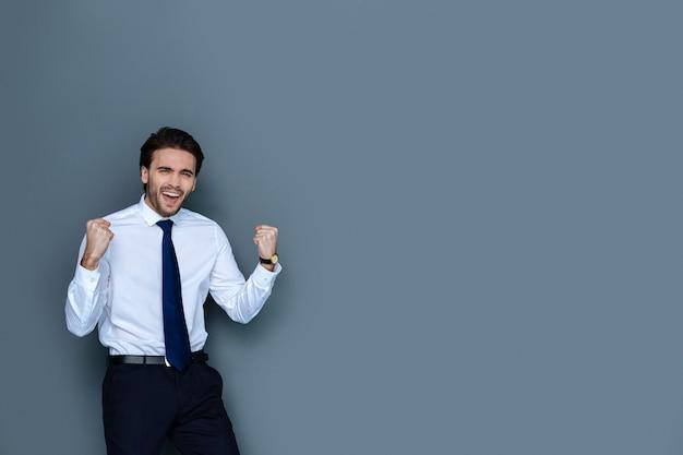 성공적인 거래. 성공적인 거래에 대해 행복하면서 직장에서 자신의 감정을 표현하는 즐거운 긍정적 인 감정적 사업가