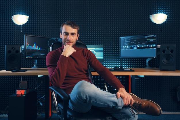 Успешный дизайнер или редактор сидит ногой к ноге в кожаном кресле и смотрит в камеру, с мониторами и звукоизоляционной стеной на заднем плане с местом для копирования