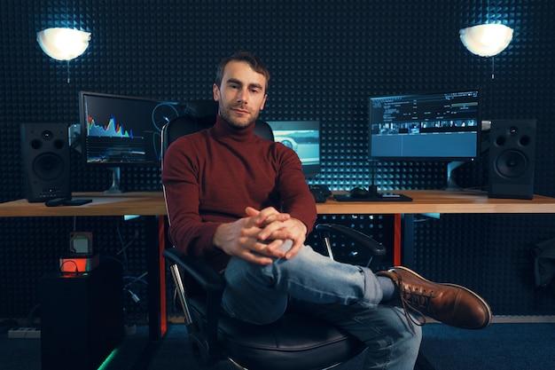 Успешный дизайнер или редактор сидит за ногой в кожаном кресле