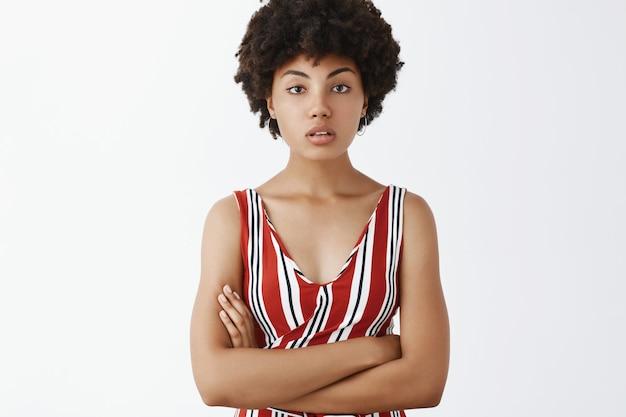 Успешная целеустремленная и красивая женщина-предприниматель афроамериканского происхождения в стильной одежде, глядя с полуоткрытым ртом, скрестив руки на груди