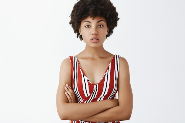 Successful determined and beautiful female african american entrepreneur in stylish clothes, staring with half-opened mouth, crossing hands on chest
